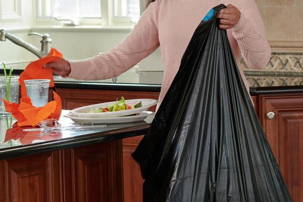 Person throwing kitchen waste into a Strong Drawstring Trash Bag.